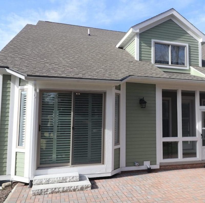 home with green siding and black shingle roof
