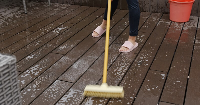 soapy water and broom being used to care for and clean a trex deck