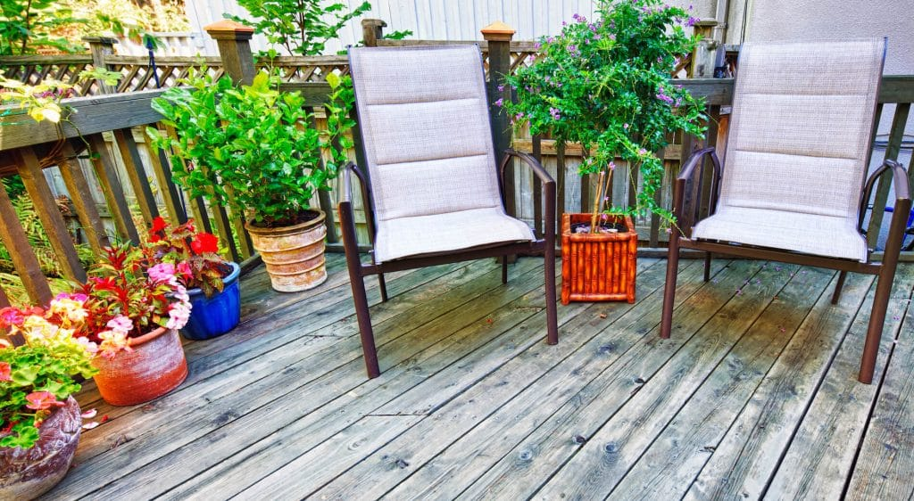 deck with potted plants and chairs provides comfort that makes it worth adding a deck to your home
